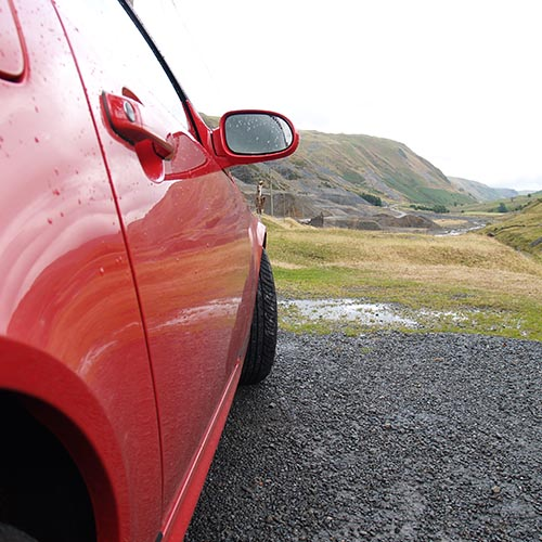 Red car parked near old shale piles