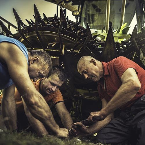 Farmers fixing a tractor