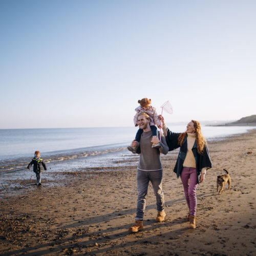 Three generation family enjoying walking along the coast. Its cold outside so they are wrapped up warm.